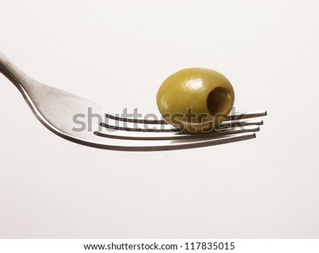 Green olive on a fork. - stock photo