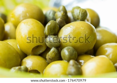 Green olives and capers in bowl, closeup, Italian ingredients, macro - stock photo