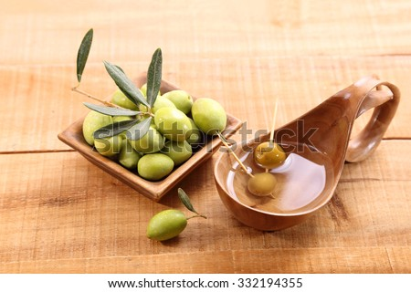 Green olives and oil in a ladle made of olive wood on the table - stock photo