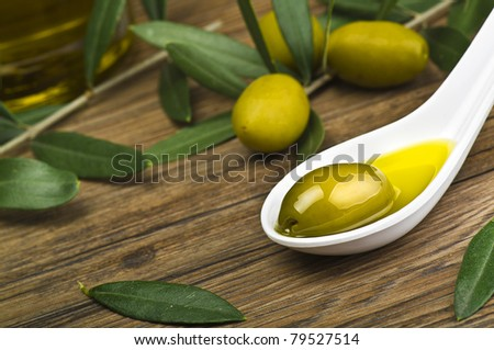 green olives and oil on the spoon - stock photo