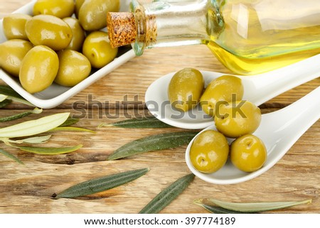 green olives and olive oil on wooden surface - stock photo