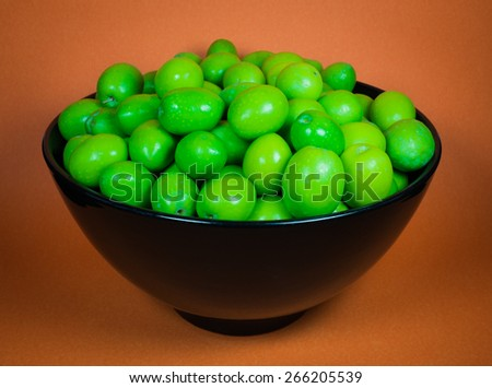 Green Olives in Black Bowl against Orange Background