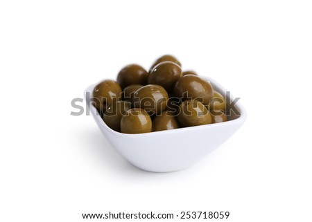 Green olives in bowl isolated on white - stock photo
