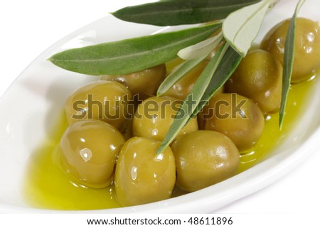 Green olives in olive oil with branch on a plate - stock photo