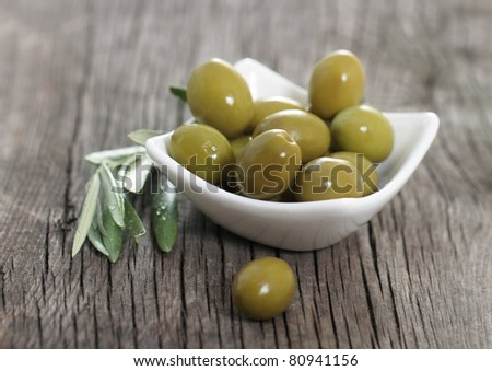 Green olives in the bowl and olive branch on wooden table - stock photo