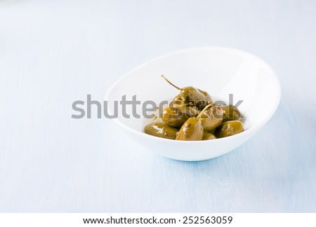Green olives marinated with coriander in white bowl on light blue background, copy space, selective focus - stock photo