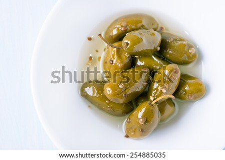 Green olives marinated with coriander in white bowl, top view, copy space, selective focus - stock photo