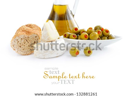 Green olives, oil, slices of bread and cheese are on a white background