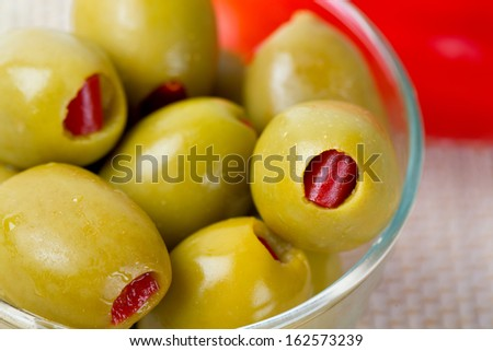 Green olives stuffed with red paprika