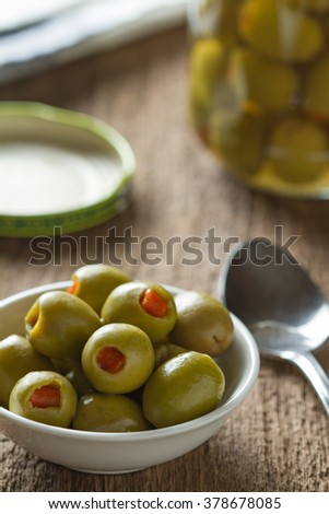 Green olives stuffed with red paprika in bowl on table. - stock photo