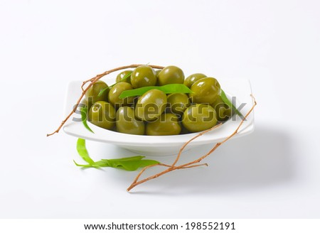 green olives tapas, decorated with leaves and twigs - stock photo