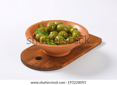 green olives with stones, served in the bowl with cutting board - stock photo