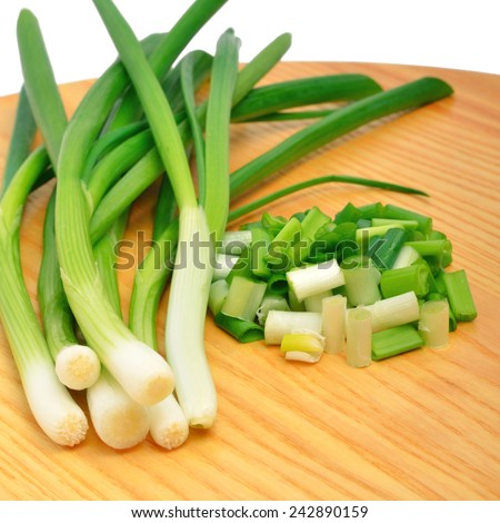 Green onion on the wooden board isolated on white - stock photo