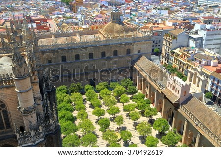 Green orange trees decorate the cloister of the Cathedral of Saint Mary of the See (Seville Cathedral) in Seville, Andalusia, Spain - stock photo