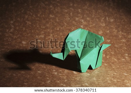 Green origami elephant isolated on craft paper background. - stock photo