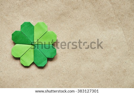 Green origami paper shamrock clover leaf on eco paper background. St. Patrick's Day greeting postcard template. Space for copy, text, lettering. - stock photo