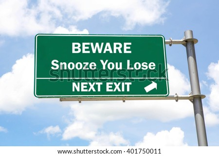 Green overhead road sign with a Beware of a Snooze You Lose Next Exit concept against a partly cloudy sky background. - stock photo