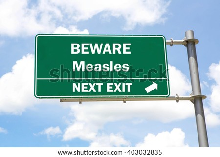 Green overhead road sign with a Beware of Measles Next Exit concept against a partly cloudy sky background. - stock photo