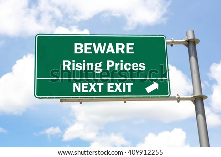 Green overhead road sign with a Beware Rising Prices Next Exit concept against a partly cloudy sky background. - stock photo
