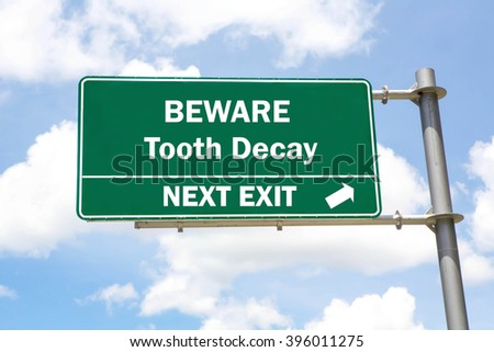 Green overhead road sign with a Beware Tooth Decay Next Exit concept against a partly cloudy sky background. - stock photo