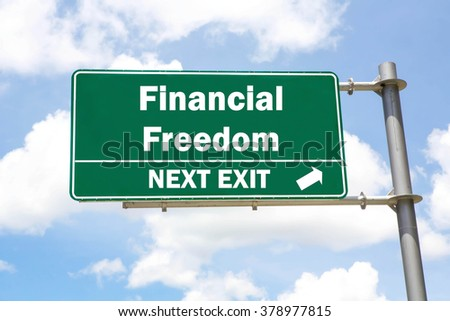 Green overhead road sign with a Financial Freedom Next Exit concept against a partly cloudy sky background. - stock photo