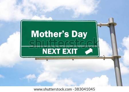 Green overhead road sign with a Mother's Day Next Exit concept against a partly cloudy sky background. - stock photo