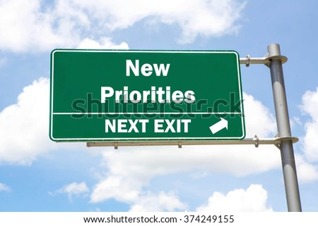 Green overhead road sign with a New Priorities Next Exit concept against a partly cloudy sky background. - stock photo