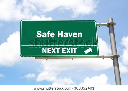 Green overhead road sign with a Safe Haven Next Exit concept against a partly cloudy sky background. - stock photo