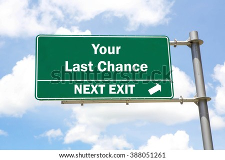 Green overhead road sign with a Your Last Chance Next Exit concept against a partly cloudy sky background. - stock photo