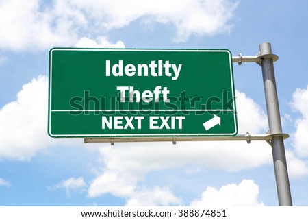 Green overhead road sign with an Identity Theft Next Exit concept against a partly cloudy sky background. - stock photo