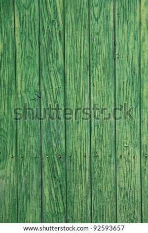Green paint peeling from a wooden panel door. Aged texture - stock photo