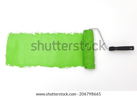 Green paint roller on white background - stock photo