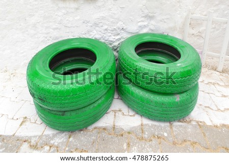 green painted car tires near a white wall