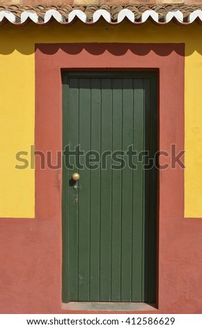 Green painted wooden door in red and yellow wall. Funchal, Madeira, Portugal - stock photo