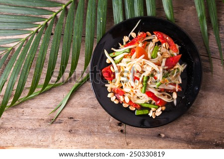 green papaya salad  in black plate on wooden background - stock photo
