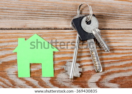 Green paper house figure with keys on wooden background.