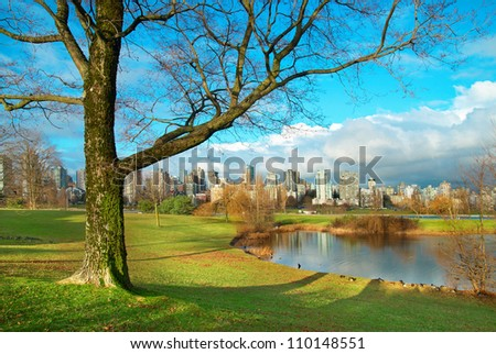 Green park near sea front with skyscrapers on the background. Vancouver, Canada. - stock photo
