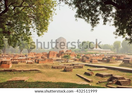 Green park with ruined temple walls and sacred Dhamekh Stupa in Sarnath. Indian landmark, place where Gautama Buddha first taught the Dharma at 500 BC. - stock photo