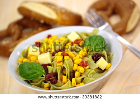 Green Pasta Salad with Corn and Kidney Beans,dried tomatoes - stock photo
