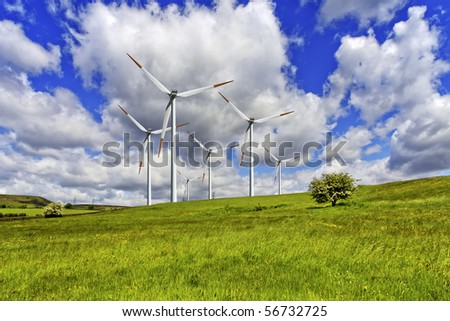 Green pasture and wind turbines farm - stock photo