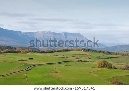 green pastures and mountains on a spring morning - stock photo