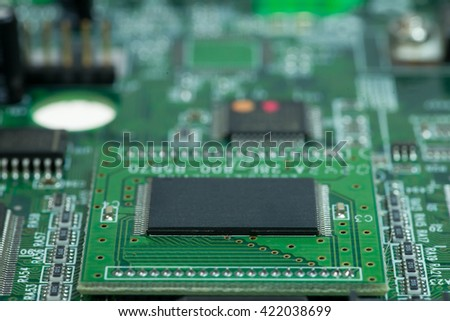 green pcb board with microchips with bokeh