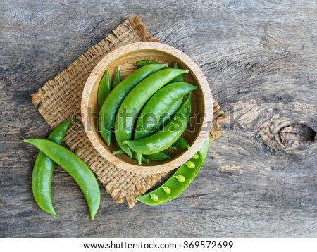 Green pea in bowl of top view on rustic wooden background with copy space - stock photo