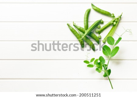 green pea pod on white wooden table table - stock photo