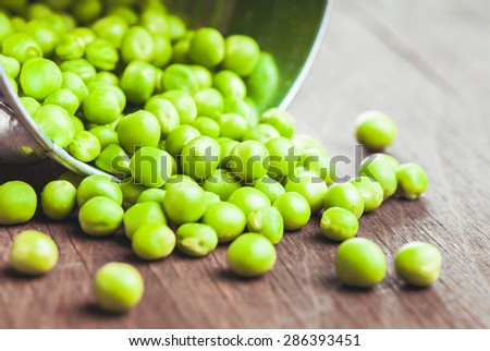 Green pea scattered on the wooden table - stock photo