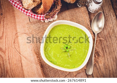 Green pea soup in a bowl with bread and sour cream on rustic line tablecloth - stock photo