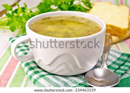 Green pea soup in a white bowl on a napkin, bread, spoon, parsley on a background of a linen tablecloth