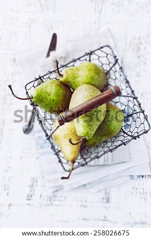 Green pears in a rustic basket - stock photo
