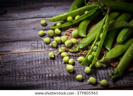 Green peas and open pea pods. Selective focus, toned - stock photo