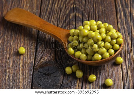 Green peas canned in spoon on old wooden table - stock photo